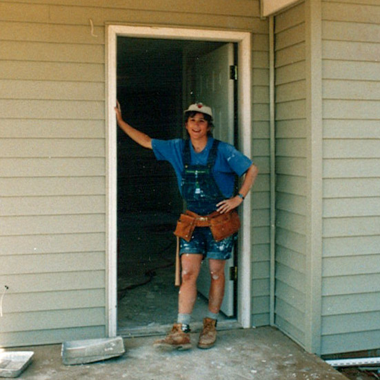 Karen wearing a tool belt standing in doorway of home.